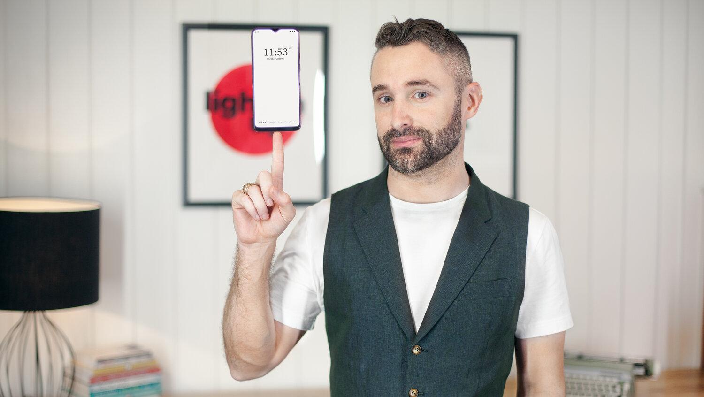 Chris Kaspar balancing a Wisephone smartphone on his finger.