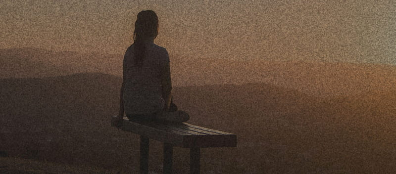 Silhouette of lady on bench watching the sunset over hills and mountainscape.
