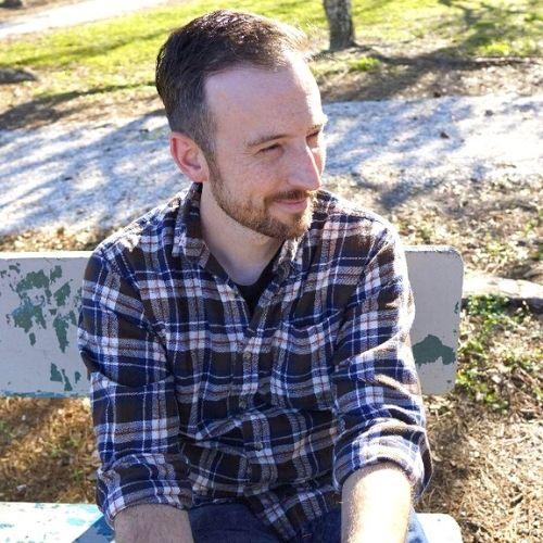 Man smiling on bench.