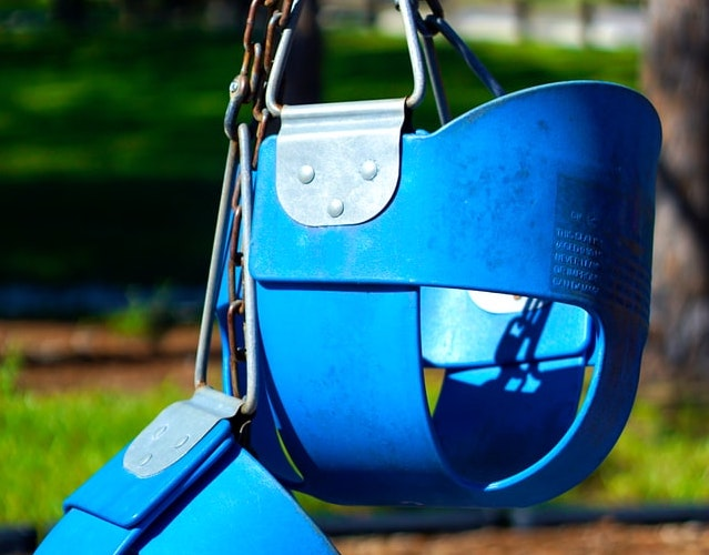 Two blue child playground swings locked together during the pandemic / COVID 19.